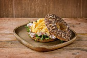 Opened Whole Grain bagels with scrambled eggs, pea sprout and prosciutto ham on wood plate