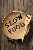 'Slow Food' written on a wooden plate with a fork