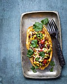 Baked spaghetti squash filled with black beans, sweetcorn and jalapeños
