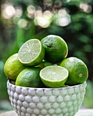 Fresh limes, whole and halved, in a ceramic bowl