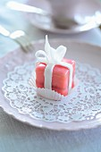A pink petit four on a paper doily