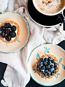 Two berry tarts and a cappuccino