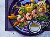 Prawn skewers on salad with a lime and ginger sauce and sesame seeds