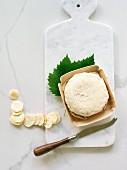 Robiola mit Weinblatt und Käsemesser auf Käsebrett