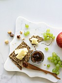 White Cheddar cheese block with crackers, grapes and jam