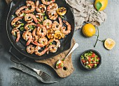 Grilled tiger prawns in cast iron grilling pan with lemon, leek, chili pepper and mint salsa sauce
