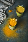 Golden milk with turmeric powder in glasses over dark grunge background
