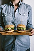 A woman is holding two guacamole burgers in her hand on a wood cutting board