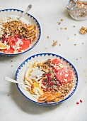 Healthy breakfast yogurt bowls with granola, grapefruit, banana, pomegranate, dried fruit, nuts and seeds
