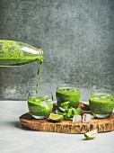 Fresh green smoothie in glasses and pouring from bottle with ice cubes, mint, lime on wooden board