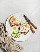 Breakfast toast with fried eggs with vegetables on white plate over grey marble background, top view