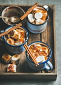 Hot chocolate in enamel mugs with cinnamon and roasted marshmallows in wooden tray