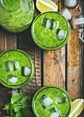 Fresh green smoothie in bottle and glasses with ice cubes, mint and lime in wooden tray, top view