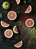 Sliced pink tiger lemon with mint leaves on branches with pink and green powder