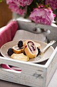 Sponge roll with blackberries and plums