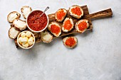 Salmon red caviar in bowl and Sandwiches on wooden cutting board on white background