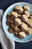 Mürbeteigplätzchen mit Schokoglasur und Kurkuma-Zucker auf Teller