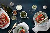 Ofenpaprika gefüllt mit schwarzem Reis, Tomaten und Mozzarella, dazu Basilikumöl und Wein