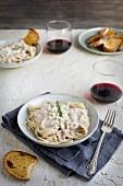 Spaghetti mit Gorgonzola-Rosmarinpesto serviert mit Brot und Wein