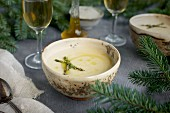 Asiago White Bean Soup with Thyme Oil served in ceramic bowls with white wine on a gray background