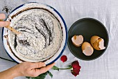 Hands stirring a mixture of flour, chocolate and cocoa powder in a mixing bowl with eggshells and a red rose