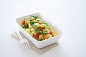 Tortellini with vegetables in a takeaway box