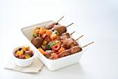 Pork skewers with vegetable sauce in a takeaway box