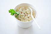 Rice with pepper and parsley in a takeaway pot