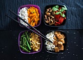 Vier Schalen mit Reis, gebratenen Karotten, Champignons, Paprika, Bohnen, Mungobohnen, Mie-Nudeln und Tofu (vegan)
