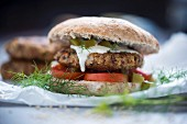 A burger with a millet fritter, tomato, and a dill and cucumber sauce (Vegan)