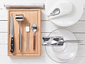 Kitchen utensils for making beef carpaccio with mushrooms, rocket and Parmesan
