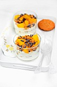 Creamy yoghurt with muesli, canned peaches and chocolate rolls