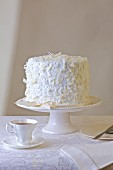 White chocolate and vanilla cake with white tea cup and white background