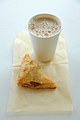 Coffee in a paper cup and apple turnover on a napkin