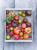 A crate of tomatoes on a wooden background (top view)