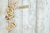 Peanuts with a brown paper label on a wooden background (top view)