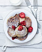 Banana pancakes with strawberries and icing sugar