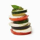 A tower of tomato, courgette, aubergine, mozzarella and pesto