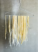 Homemade tagliatelle hanging on a wire coat hanger to dry