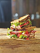 A roast beef sandwich with cucumber, tomato and guacamole