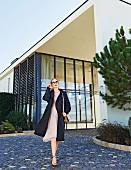 Rothaarige Frau in Trenchcoat im Oversize-Look und rosafarbenem Sommerkleid