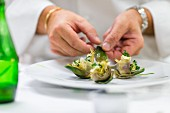 A chef arranges marinated artichokes on a plate