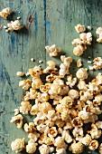 Popcorn covering an aqua blue green wooden surface