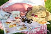 Picknickdecke auf der Wiese mit Kaffee, Strohhut und Zeitschrift