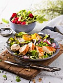 A mixed leaf salad with a chicken fillet, radishes and pine nuts