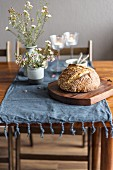 Bread and flowers on rustic wooden table