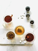 Assortment of teas in clear cups on white with tea leaves
