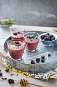 Berry smoothie in glasses with honey and berries