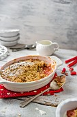 Rhubarb crumble in a baking dish with a jug of cream behind and fresh rhubarb
