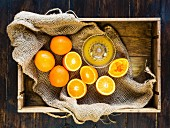Box of fresh oranges - some squeezed to make fresh orange juice